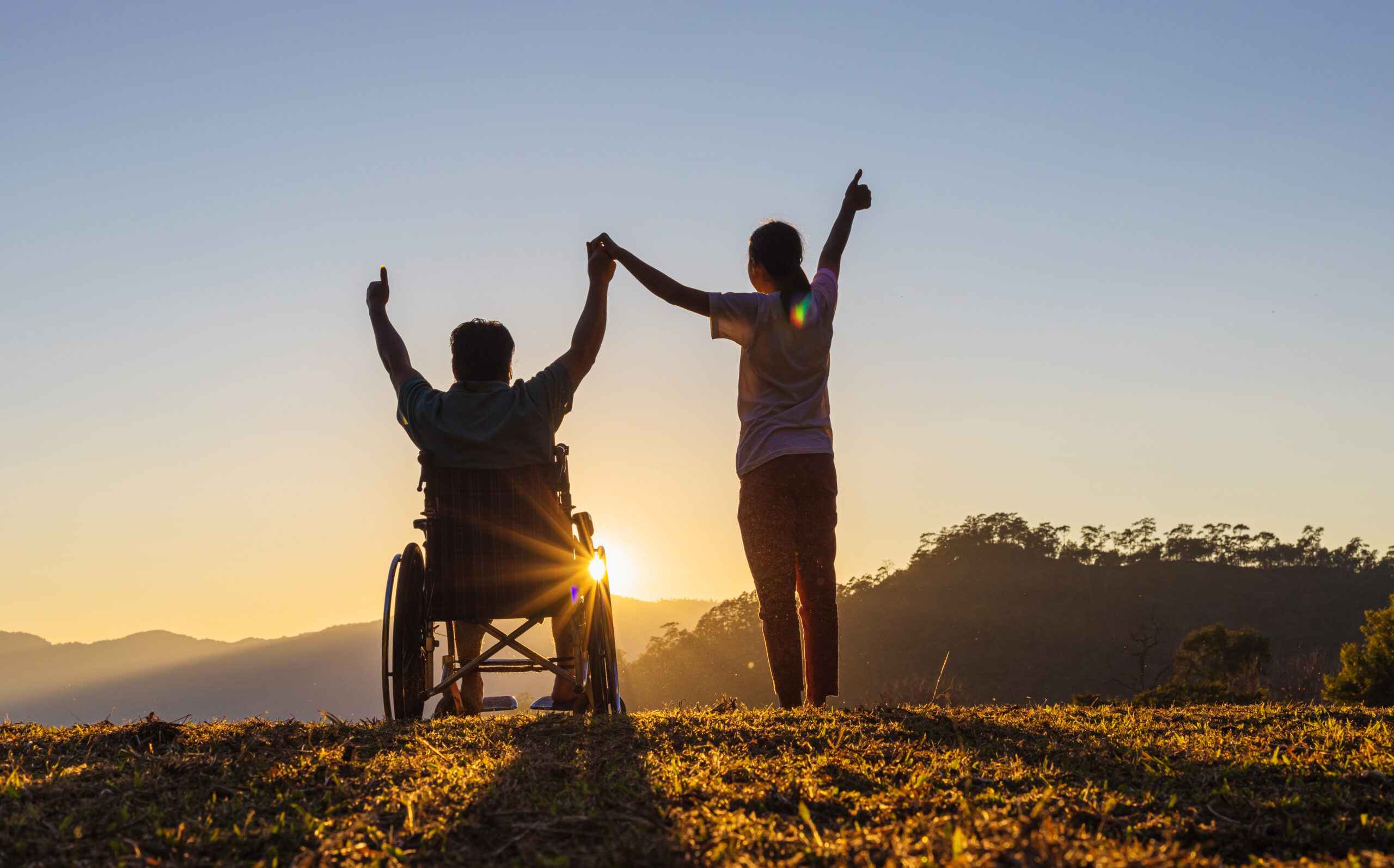 Two people stood on top of a hill watching the sunrise