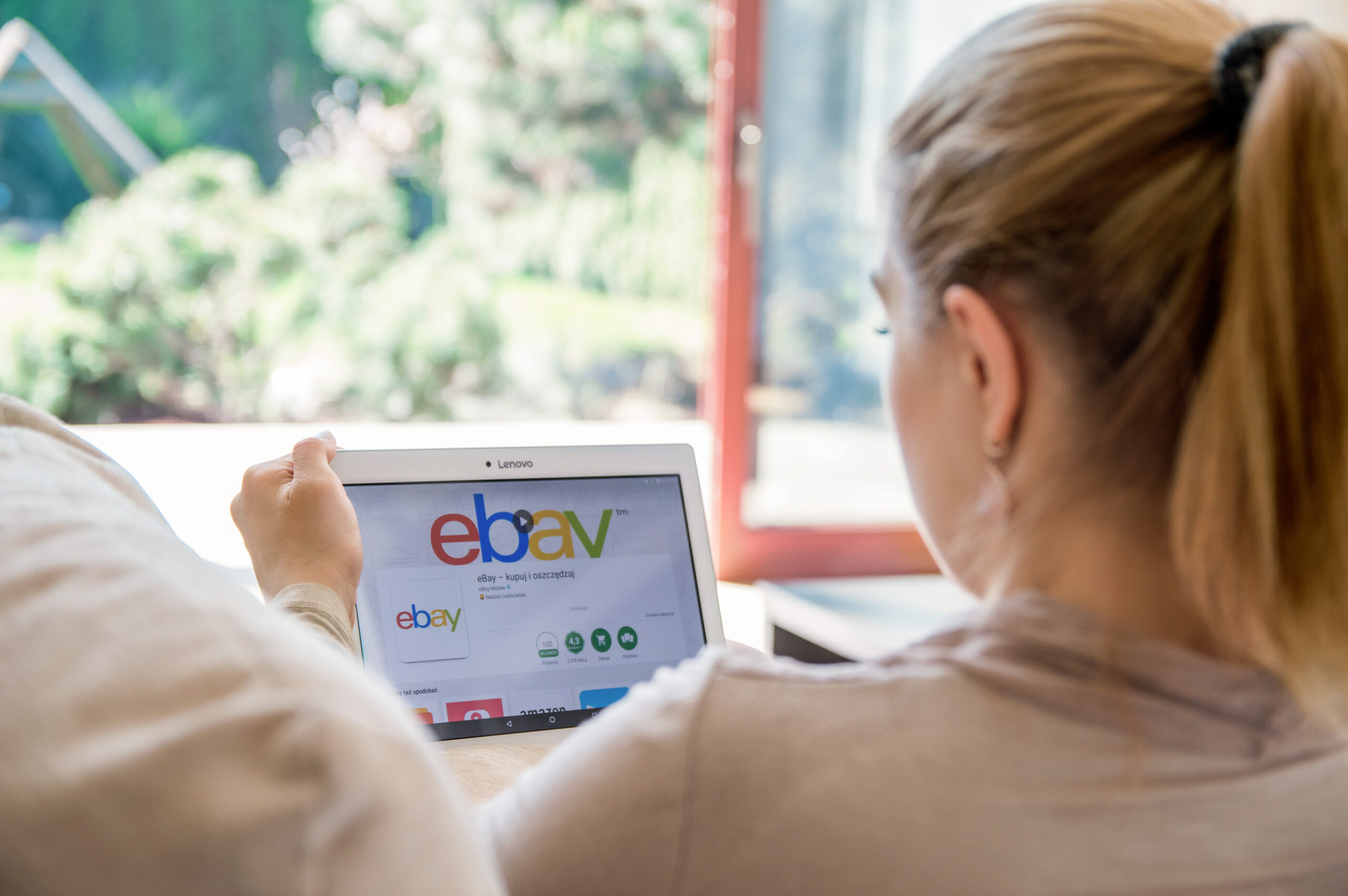 A woman looking at eBay on a computer tablet